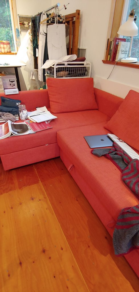 A photograph of a couch with books, papers and a laptop strewn around.